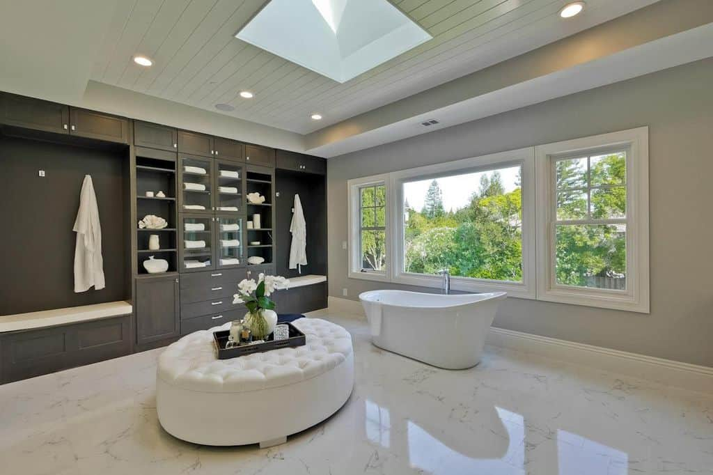 Large primary bathroom boasts a freestanding bathtub and a white tufted ottoman along with a full height cabinet that's fitted with a built-in seat nook. It has white marble flooring and a shiplap ceiling fitted with a skylight and recessed lights.