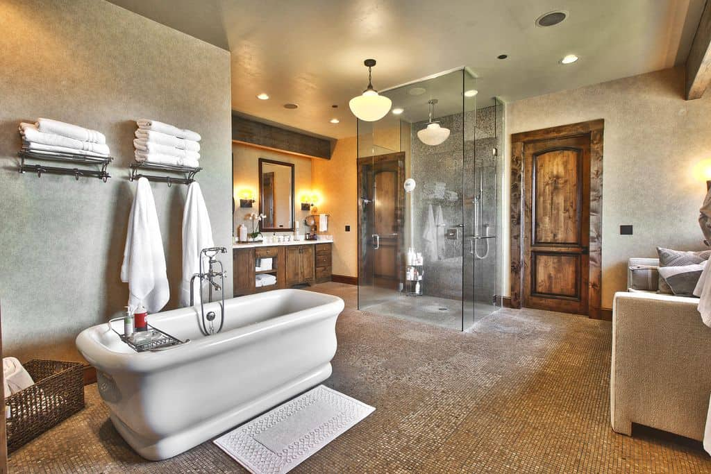A cozy gray seat filled with fluffy pillows faces the walk-in shower and marble top vanity that's paired with a wooden framed mirror. It is accompanied by a freestanding tub that's complemented by a rattan basket and a white textured rug laying on the mosaic tile flooring.