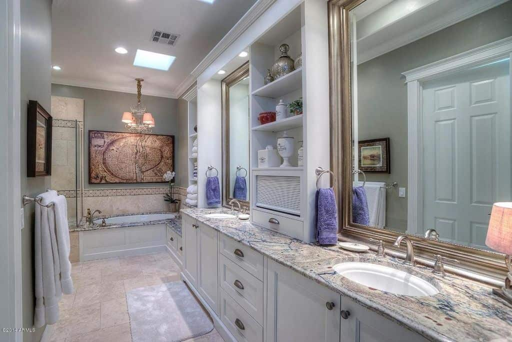 A large artwork highlights the drop-in tub that's illuminated by a warm chandelier along with recessed ceiling lights and a small skylight. Attached to it is a built-in seat following by a dual sink vanity with granite countertop and open shelving.