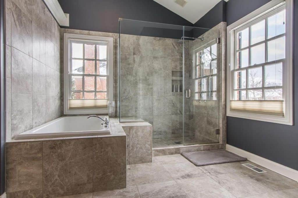 Gray primary bathroom with a cathedral ceiling and beige tiled flooring extending to the bathtub surround and backsplash. It has a walk-in shower and white framed windows that bring plenty of natural light in.