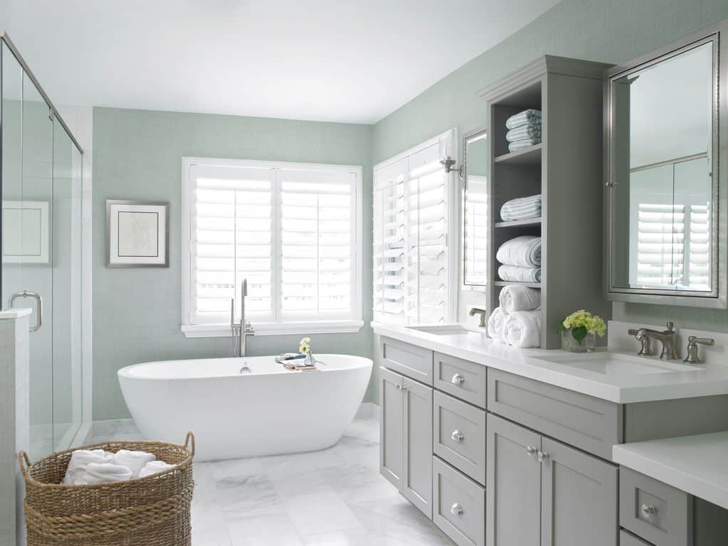 The bright primary bathroom features a freestanding tub by the louvered window along with dual sink vanity that's topped with open shelving flanked by mirrored medicine cabinets.