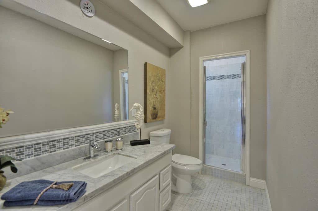 Marble top vanity paired with a frameless mirror along with a walk-in shower flanked the traditional toilet over white tiled flooring. It is surrounded by gray walls that are adorned by a gorgeous floral artwork.