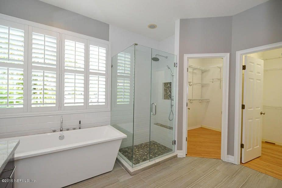 A freestanding tub under louvered windows sits beside the walk-in shower with an inset shelf and a tiled bench. Next to it is another two areas with white walls and hardwood flooring.
