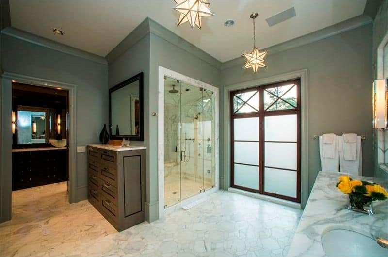 Star pendant lights illuminate this primary bathroom showcasing wooden vanities and a walk-in shower facing the dual sink vanity. It has gray walls and a marble tile flooring arranged in a hexagon pattern.