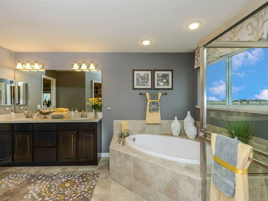 This primary bathroom is decorated with floral artworks and a patterned valance covering the glazed windows that overlook an expansive view. It is filled with dark wood vanity and a drop-in tub complemented by a gray printed rug.