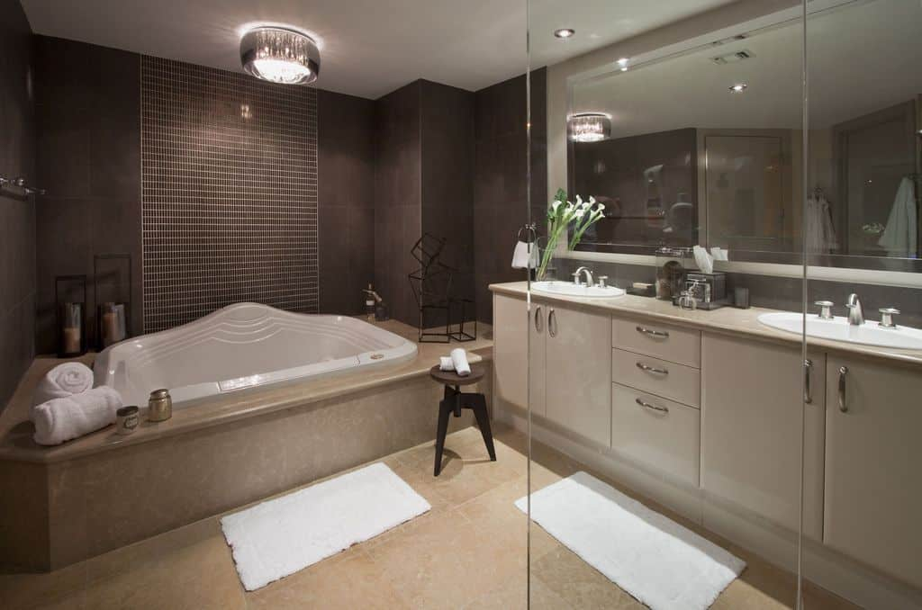 A classy flush mount light illuminates the deep soaking tub that's topped with a geometric decor and metal candle holders. It is accompanied by a dual sink vanity and round stool along with white shaggy rugs that lay on the beige tiled flooring.