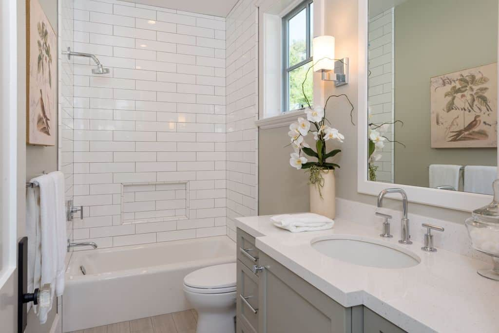 Interesting artworks add a nice accent in this gray bathroom with a glass framed window and a traditional toilet flanked by marble top vanity and a shower and tub combo.
