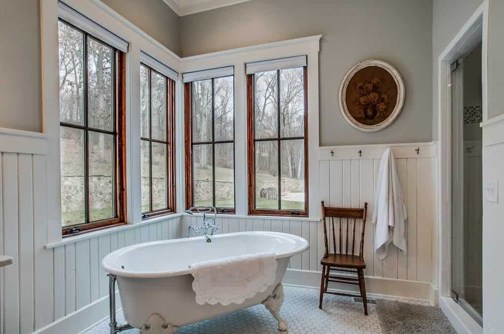 Country style bathroom showcases beadboard walls accented with a round floral artwork along with a wooden framed windows overlooking the enchanting forest. It is filled with a walk-in shower and a clawfoot tub that's paired with a wooden chair over hex tile flooring.