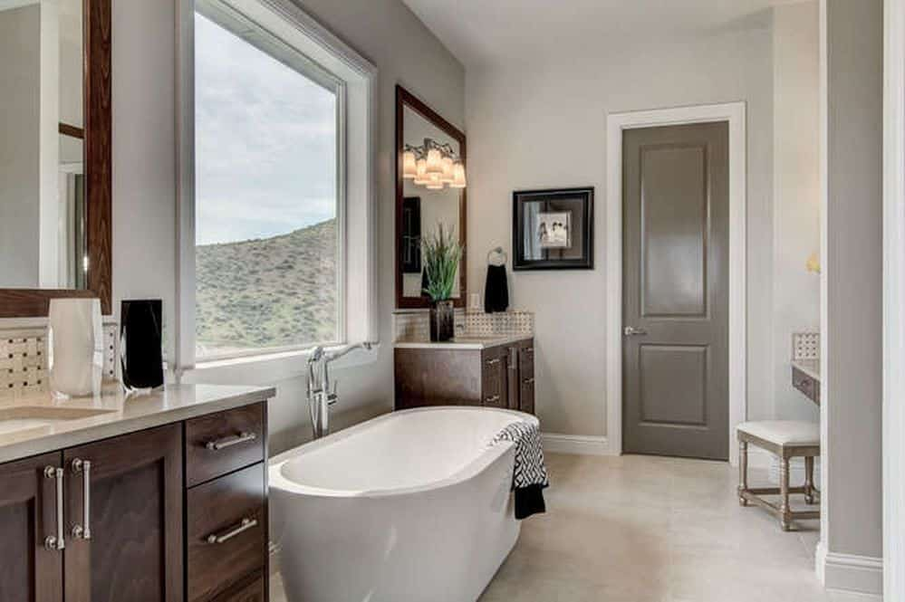 Dark wood vanities flanked a freestanding tub by the picture window with a stunning mountain view. It is accompanied by a black framed wall art and a cushioned stool over beige tiled flooring.