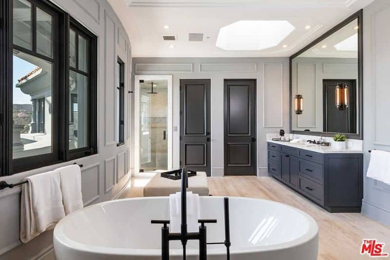 Linear sconces mounted on the large mirror illuminate the marble top vanity that's fixed against the gray wainscoting. It is accompanied by a walk-in shower and a beige ottoman along with a freestanding tub fitted with wrought iron fixtures.