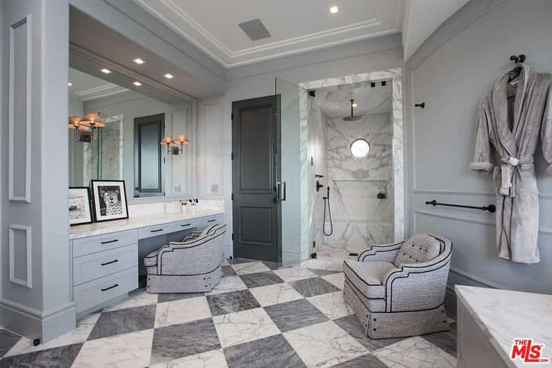 The opposite side of the deluxe primary bathroom showcasing a marble top vanity and charming gray seats along with a walk-in shower that's fitted with an inset shelf and wrought iron fixtures.