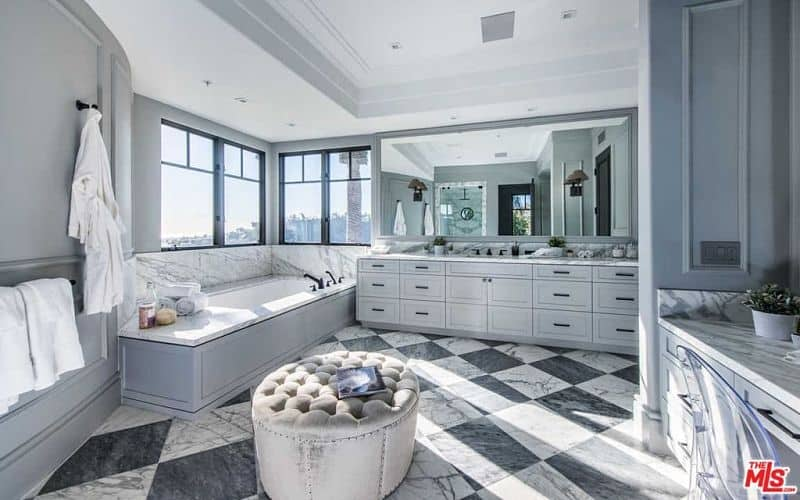 Deluxe primary bathroom with gray vanities and a deep soaking tub by the aluminum framed windows inviting an ample amount of natural light. There's a tufted ottoman in the middle that sits on a striking marble checkered flooring.