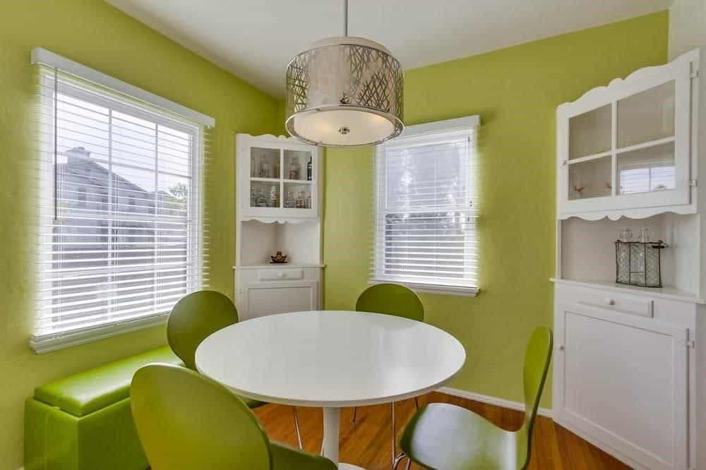 Green dining room illuminated by a stylish drum pendant along with natural light from the glazed windows covered in white roller blinds. It offers corner cabinets and a cushioned bench matching with the sleek chairs that are paired with a round dining table.
