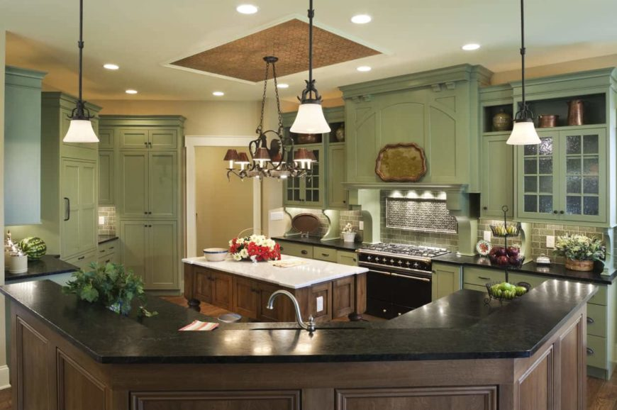 This is a lovely kitchen wherein the use of green cabinetry benefits the overall beauty of the kitchen. It offers an eye-pleasing aesthetic especially with the complement of the brown kitchen islands and the hardwood flooring as well as the brown ceiling panel and its brown chandelier.