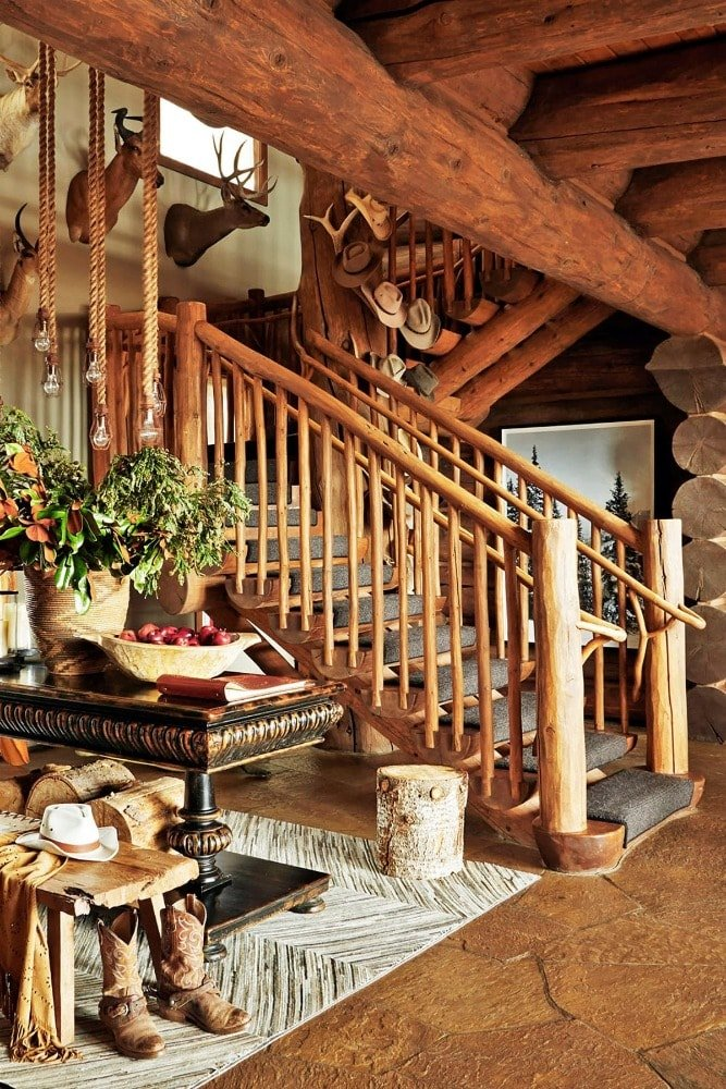 Upon entry of the house, you are welcomed by this rustic foyer with a wooden stairs, a wooden table and wooden ceiling with log beams.