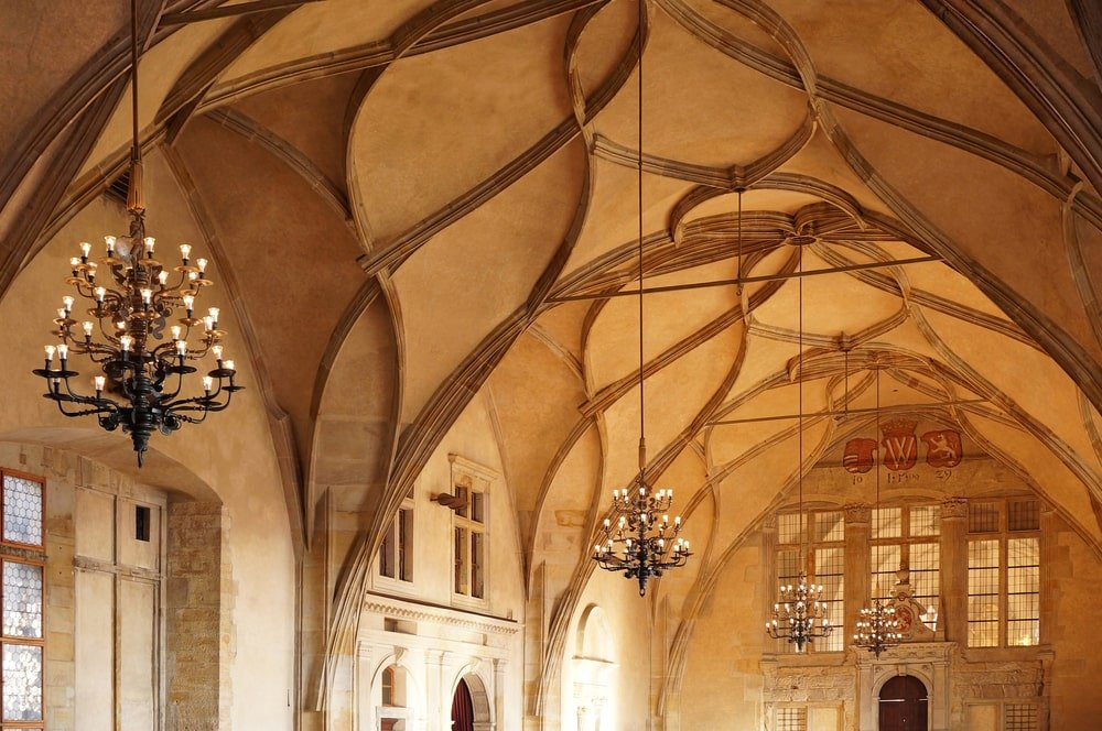 This is an elegant and high groin vault ceiling that has the same earthy beige tone of the walls and accented with embossed lines to bring out the subtle patterns of the ceiling. This is then complemented with a few hanging multi-tiered chandeliers.