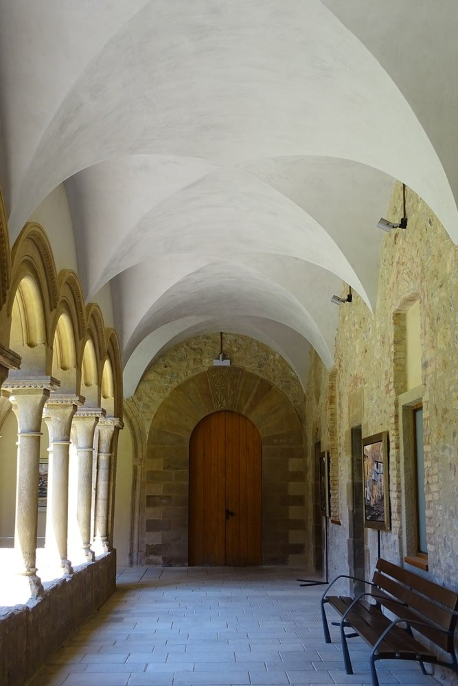 This is a simple hallway at the side of the house with a textured stone wall on one side and columns and arches on the other side that illuminates the hallway with natural lights. This is then topped with a graceful groin vault ceiling with a bright tone.