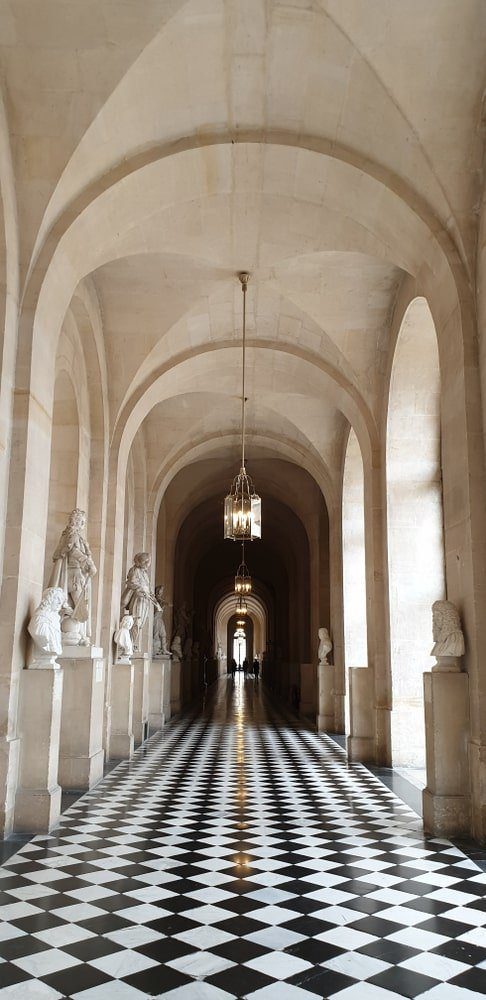 The gorgeous checkered black and white flooring of this hallway gives this area a complexity that is augmented by the detailed statues and busts on the side of the stone pillars that connect to the groin vault ceiling that has an earthy beige tone.