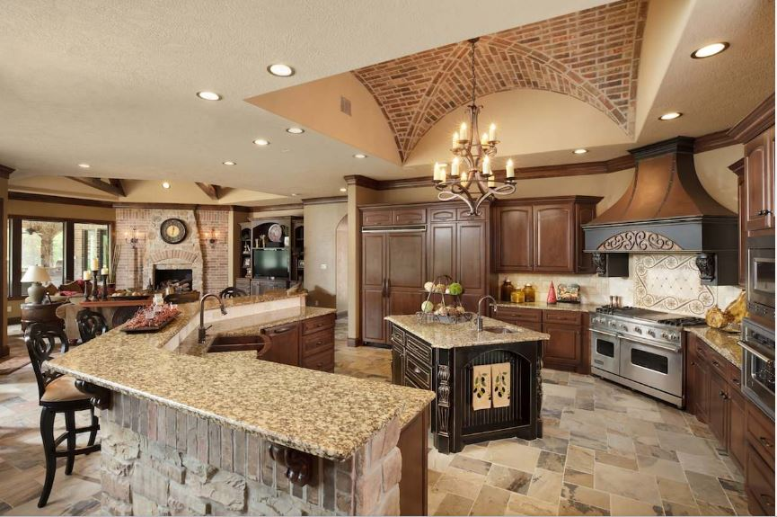 This kitchen has a beige ceiling with a depression on its middle part with a groin vault that hangs a chandelier over the small wooden kitchen island that stands out against the beige marble flooring . This is complemented by the dark brown tones of the kitchen peninsula and the second larger curved kitchen island.