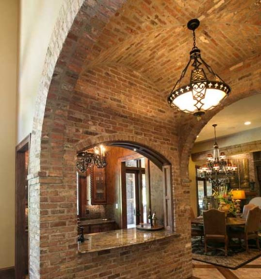 The small kitchen of this home has an arched alcove counter near the dining room for serving dishes. This arch is made of red textured bricks that extend to the groin vault ceiling where a single dome pendant light hangs from the middle point.