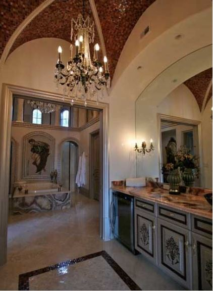 This is a small vanity area separated from the rest of the large bathroom by an entryway. This area has a gray wooden vanity fixed into the beige wall as well as its large mirror. These are then contrasted by the small dark tiles of the groin vault ceiling.