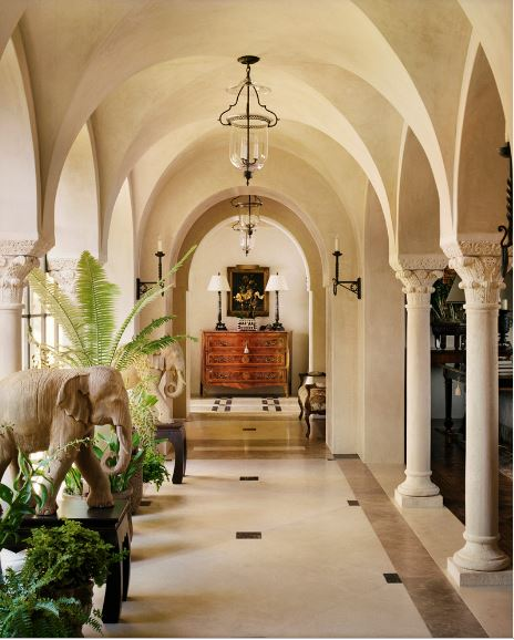 This is a brightly lit hallway that stems from the foyer. The narrow beige flooring is flanked by arches and pillars the connect to groin vaults in the ceiling with the same beige hue to make the transition smooth. These are complemented by the elephant statuettes and the potted plants on the side.