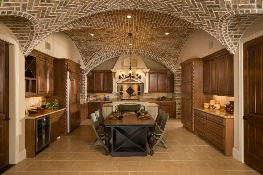 This large room that houses both the kitchen and informal dining area has a groin vault ceiling made of red bricks and hangs a small chandelier over the wooden table of the dining area. The wood top of this table matches the brown tone of the cabinetry surrounding it as part of the kitchen.