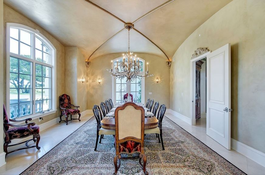 There is a long wooden elliptical dining table that is partnered with wooden dining room chairs that has cushioned seats. Their dark wooden legs stand out from the large colorful patterned rug that contrasts the beige ceiling and its groin vault ceiling.