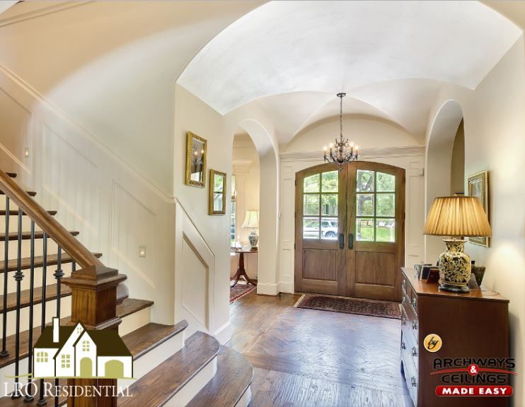 The arched wooden main doors are made of wood and glass panels. These bring in natural lighting for the matching hardwood flooring and the beige groin vault ceiling that seamlessly connects with the beige walls adorned with a cabinet on the side with a lamp.