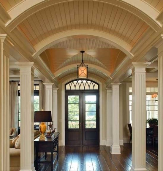 This foyer has a hallway-like design with a unique wooden shiplap ceiling combined with a groin vault ceiling in the middle that bears the lantern pendant light over the entrance beside the dark wooden console table that matches with the wooden main door.