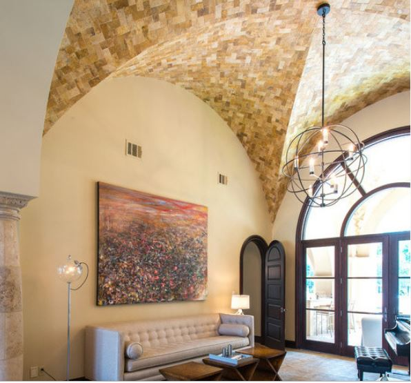 The large colorful abstract painting above the beige leather tufted sofa brings in a dash of color to complement the uniform beige walls and beige bricks that make up the groin vault ceiling with an iron spherical decorative pendant light in the middle.