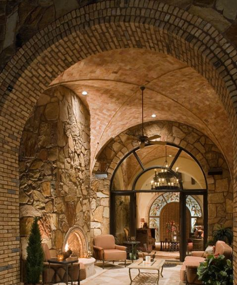 This comfortable and cozy porch has yellow lights coming from the recessed lights on the side of the groin vault red brick ceiling matching those on the stone archway. These are a good match for the textured parts of the stone wall that houses the arched fireplace facing the cushioned sofa set.