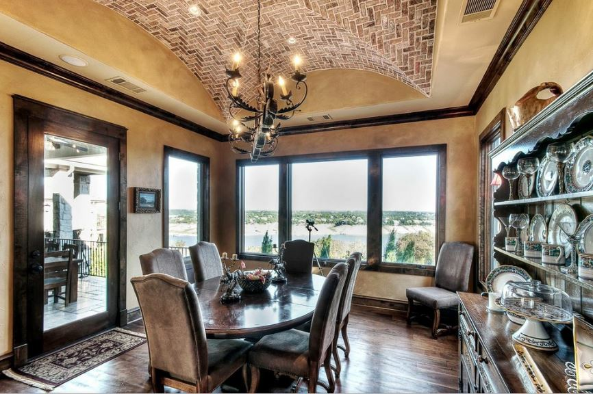 The groin vault ceiling above this charming dining room is made of red bricks that stand out against the earthy beige tone that surrounds it extending to the walls. This is contrasted by the dark wooden flooring and the dark wooden dining set.