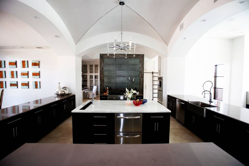 The dark elegant cabinets and drawers of the kitchen island and peninsulas that are flanking it, all have a pitch black tone that make the white countertop of the island stand out as well as the stainless steal handles and drawers matching with the chandelier frame.