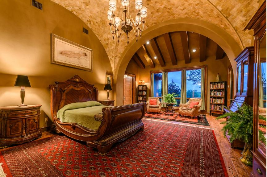 This is an incredibly sexy master bedroom with a high groin vault ceiling blending well with the earthy mustard walls that make the wooden sleigh bed stand out contrasted by the red patterned area rug that covers most of the hardwood flooring.