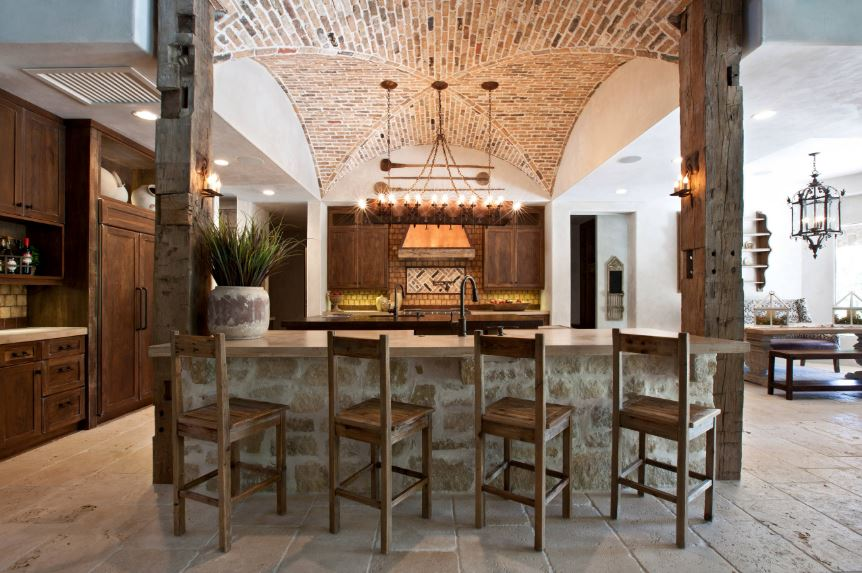 This is a beautiful Tuscan-style kitchen with a textured concrete flooring that goes well with the textured wooden columns and breakfast bar that is paired with rustic wooden stools. These are complemented by the groin vault ceiling of the kitchen made of red bricks.