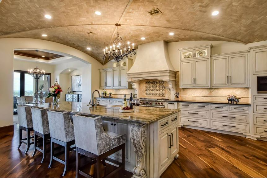 The elegant shaker cabinets and drawers of the kitchen island and peninsula are paired with dark handles and fixtures that go well with the off white tone of the cabinetry. These also pair well with the concrete ceiling that has a groin vault design and recessed lights.