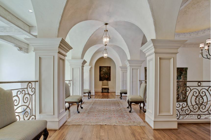 The intervals of this second floor hallway is adorned with gray cushioned chairs that go well with the wrought iron railings on each interval between the square white pillars that are all connected with the groin vault ceiling with small glass pendant lights.