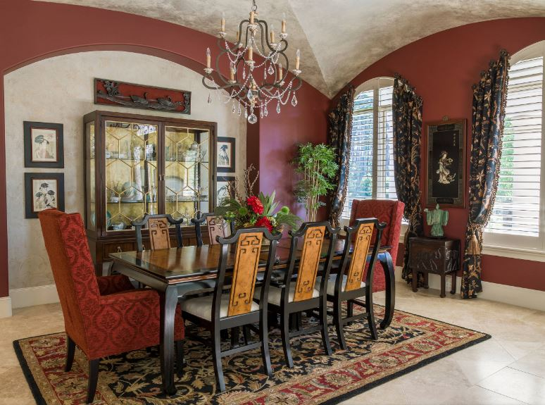 The wrought iron chandelier that has a few crystal accents stands out against the gray concrete groin vault ceiling. This is then contrasted by the dark red walls that match the scarlet patterned armchairs at each end of the rectangular dining table.