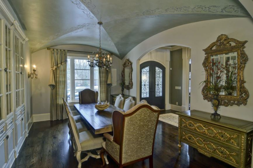 This simple dining room has a long wooden dining table that is paired with beige patterned and cushioned dining chairs that stand out against the dark hardwood flooring. These are also contrasted by the dark gray groin vault ceiling with subtle intricate patterns.