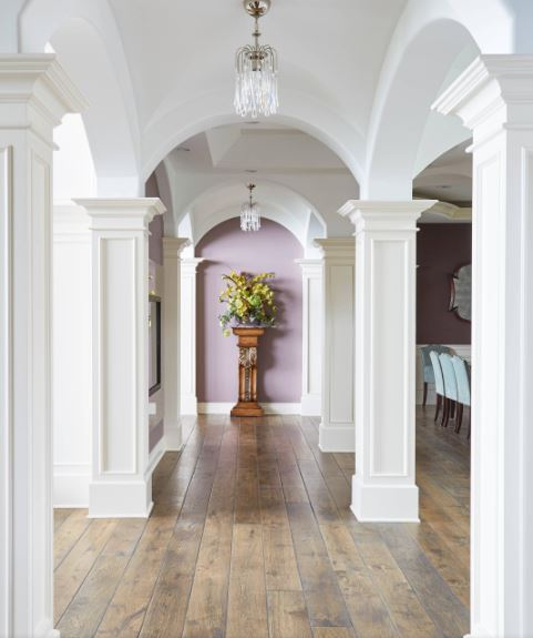 This is a beautiful and bright hallway that has white square pillars on the sides connecting to the groin arch white ceiling that contrasts the hardwood flooring. This setup is paired with a purple arched wall at the far end adorned with a pedestal that bears a potted plant.