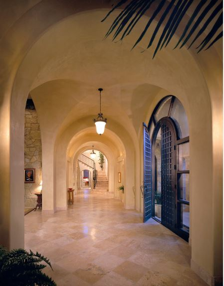 This gorgeous home has a simple and welcoming foyer with a beige groin vault ceiling to match the smooth beige marble flooring that is augmented by the pendant lights and contrasted by the dark arched main door that has glass panels on its side lights.