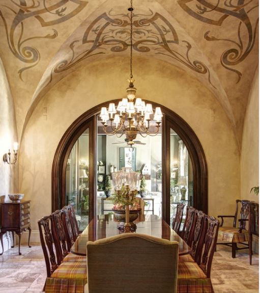 The ceiling of this charming dining room has intricate and elegant designs and patterns on its beige groin vault ceiling that hangs a simple chandelier over the long rectangular dining table that is covered with a colorful patterned table cloth.