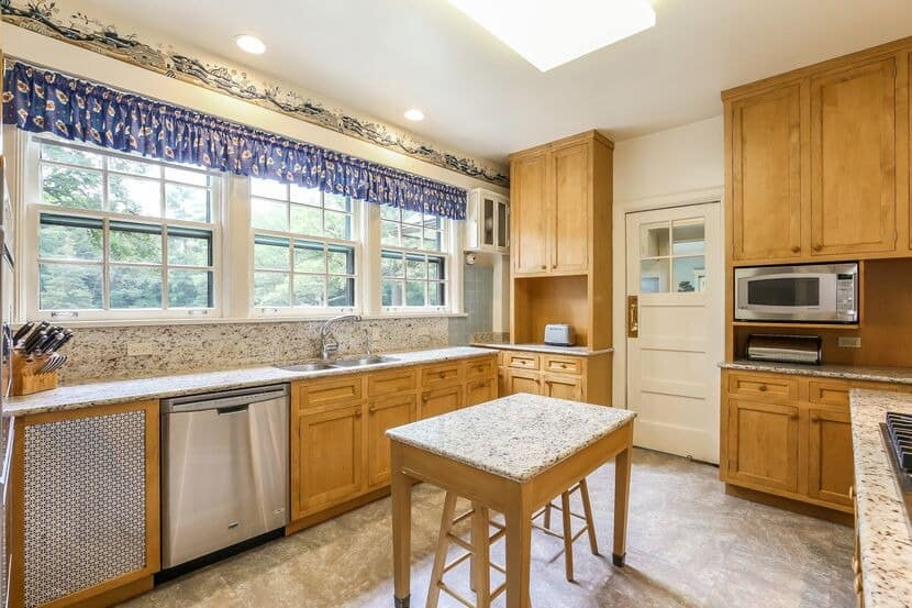 This kitchen features a gorgeous marble kitchen countertop and has brown cabinetry and kitchen drawers.