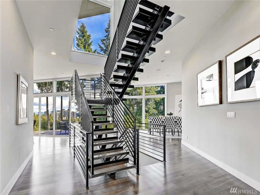 This home boasts a stylish half-turn staircase. The home features hardwood floors, gray walls and glass windows and doors.