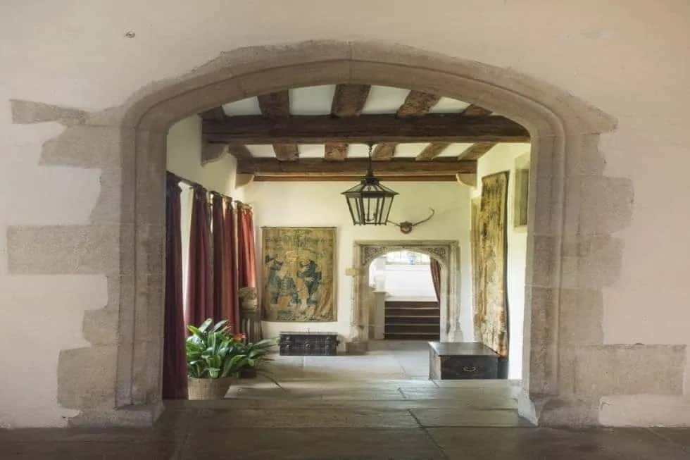 This is the stone foyer of the manor that has a beamed ceiling and large stone arches leading to the various sections of the house.