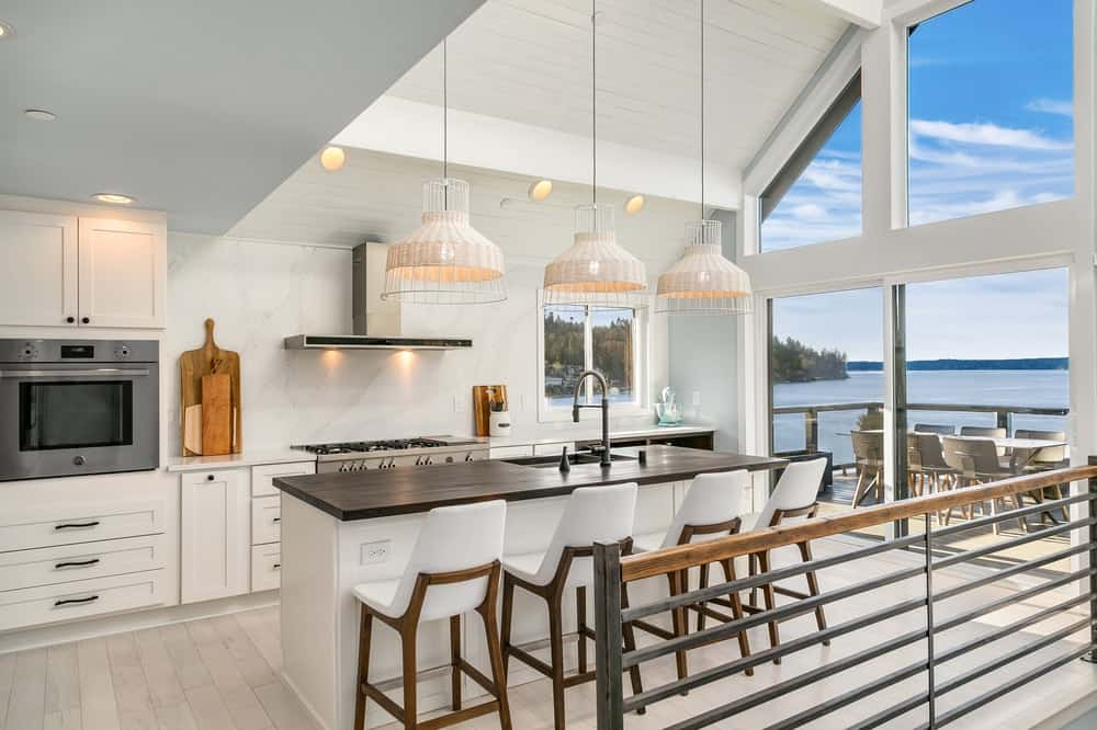 Modern kitchen area featuring a breakfast bar island lighted by a set of charming pendant lights hanging from the tall ceiling.