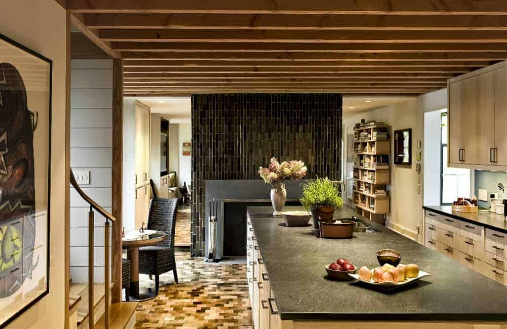 A modern kitchen area boasting a massive center island with a black marble countertop. The area also has a small dining nook table and a fireplace.