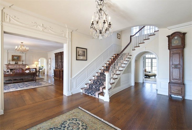 Upon entry of the house, you are welcomed by this simple foyer with a crystal chandelier, carpeted stairs and large archways leading to other rooms.