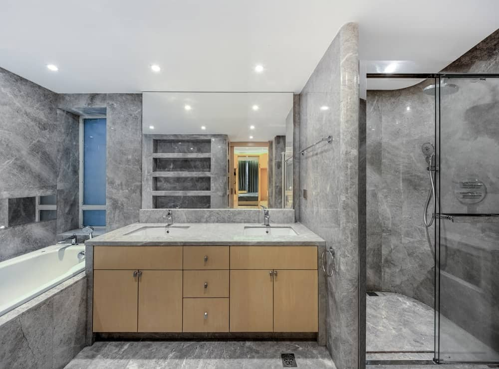 This bathroom has consistent gray marble tones on its floor, walls and the walls of the walk-in shower with a glass door by the wooden vanity.